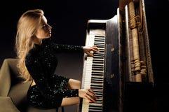 Powabna dziewczyna w wiecz?r sukni bawi? si? starego Niemieckiego pianino na widok zdjęcie royalty free