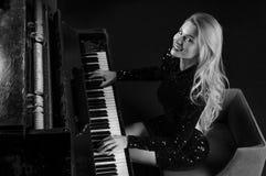 Powabna dziewczyna w wiecz?r sukni bawi? si? starego Niemieckiego pianino na widok zdjęcia stock