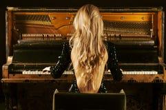 Powabna dziewczyna w wiecz?r sukni bawi? si? starego Niemieckiego pianino widok z powrotem zdjęcia royalty free