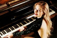 Powabna dziewczyna w wiecz?r sukni pozuje blisko starego Niemieckiego pianina widok z powrotem zdjęcie royalty free