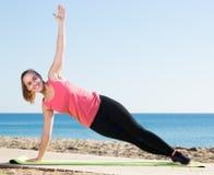 Powabna dziewczyna ćwiczy na ćwiczenie macie plenerowej Zdjęcia Stock