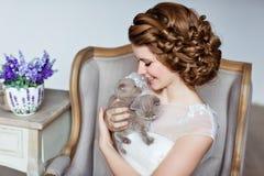 Powabna i piękna dziewczyna w biel sukni obsiadaniu w krześle, s zdjęcia royalty free