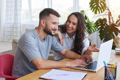 Powabna kobieta i męski dyskutować podczas gdy pracujący w laptopie Zdjęcie Royalty Free