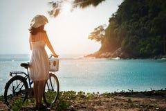 Powabna kobieta w biel sukni chodzącym bicyklu cieszy się błękitnego morze Obrazy Stock