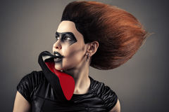 Powabna kobieta z ciemną makeup i bujny fryzurą z piętą w usta fotografia royalty free