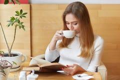 Powabna kochająca dziewczyna bierze łyczki herbata, czyta akcja pakującą książkę, skupia się wszystkie uwagę na fabule Potomstwo  zdjęcia royalty free