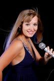Powabna młoda blondynka na czarnym tle z mikrofonem obrazy royalty free