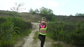 Powabna młoda blondynki dziewczyna trenuje outdoors w sporta mundurze zbiory wideo