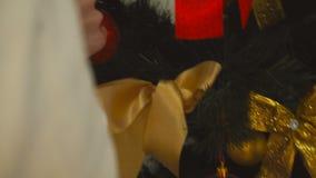 Powabna młoda dziewczyna dekoruje choinki z jaskrawą czerwoną piłką zbiory