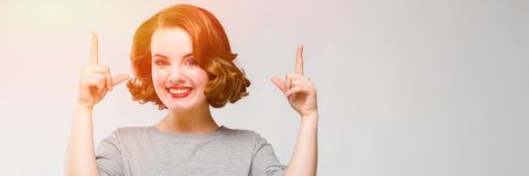 Powabna młoda dziewczyna w szarej koszulce na szarym tle Dziewczyna wskazuje palce oddolnych obrazy stock