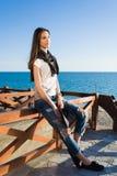 Powabna młoda kobieta cieszy się dobrą pogodę i odtwarzanie synchronizujemy podczas gdy siedzący przeciw morzu w pogodnym popołud Obrazy Royalty Free