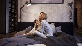 Powabna młoda kobieta w piżamach siedzi w łóżku i pije ranek kawę, obraz royalty free