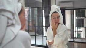 Powabna młoda kobieta z ręcznikiem na głowie przed lustrem koncentruje na jej skórze po prysznic, śmietanki jej twarz zdjęcie wideo