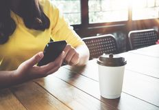 Powabna młoda modniś dziewczyna wręcza używać na jej mądrze telefonu obsiadaniu przy drewnianym stołem w sklep z kawą Obraz Stock