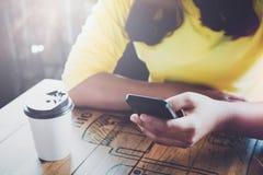 Powabna młoda modniś dziewczyna wręcza używać na jej mądrze telefonu obsiadaniu przy drewnianym stołem w sklep z kawą Zdjęcia Royalty Free