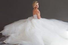 Powabna młoda panna młoda w luksusowej ślubnej sukni dziewczyny dosyć biel Szary tło plecy Fotografia Royalty Free