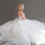 Powabna młoda panna młoda w luksusowej ślubnej sukni dziewczyny dosyć biel Szary tło plecy Zdjęcia Royalty Free