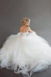 Powabna młoda panna młoda w luksusowej ślubnej sukni dziewczyny dosyć biel Szary tło plecy Obrazy Royalty Free