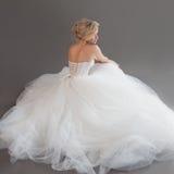 Powabna młoda panna młoda w luksusowej ślubnej sukni dziewczyny dosyć biel Szary tło plecy Fotografia Stock