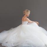 Powabna młoda panna młoda w luksusowej ślubnej sukni dziewczyny dosyć biel Szary tło plecy Zdjęcie Stock
