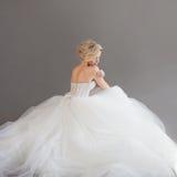 Powabna młoda panna młoda w luksusowej ślubnej sukni dziewczyny dosyć biel Szary tło plecy Obrazy Stock