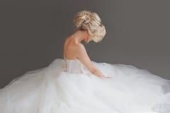 Powabna młoda panna młoda w luksusowej ślubnej sukni dziewczyny dosyć biel Szary tło plecy Obraz Stock