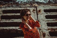 Powabna młoda uśmiechnięta kobieta patrzeje kamerę w czerwieni sukni z krótkim kędzierzawym włosy Żeńscy retro słońce ochrony oku fotografia stock