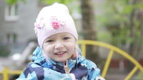 Powabna mała dziewczynka jedzie huśtawkę Zakończenie szczęśliwy dziecko zdjęcie wideo
