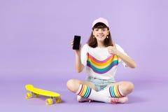 Powabna nastoletnia dziewczyna siedzi blisko deskorolka trzyma telefon kom?rkowego z puste miejsce pustym ekranem, pokazuje kciuk obraz royalty free