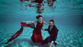 Powabna panna młoda w czerwonej sukni i fornala nur pod wodą dno basen, uśmiech i uściśnięcie, swobodny ruch zdjęcie wideo