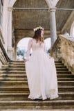 Powabna panna młoda w długiej białej ślubnej sukni i kwiecistym wianku iść w dół antyka kamienia schodkami Obraz Royalty Free