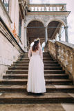 Powabna panna młoda w długiej białej ślubnej todze i kwiecistym wianku iść up antyka kamienia schodkami Zdjęcia Stock