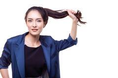 Powabna piękna kobieta ciągnie ona długie włosy dla udowadniać th zdjęcia stock