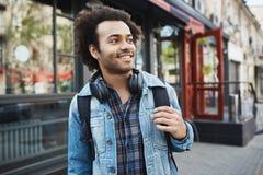 Powabna przystojna afroamerykańska samiec patrzeje na boku z szczecina i afro ostrzyżeniem podczas gdy trzymający plecaka i space Fotografia Stock