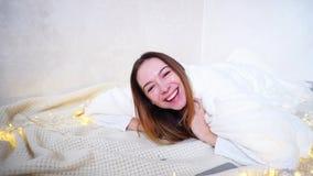 Powabna rozochocona dziewczyna śmia się wokoło i błaź się, kłamający na podłoga zakrywającej z koc w jaskrawym pokoju obok girlan zbiory