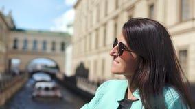 Powabna uśmiechnięta mody kobieta cieszy się światło słoneczne przy woda miejska kanałem z łodzią przy tłem zdjęcie wideo