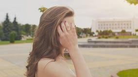 Powabna zmysłowa młoda dziewczyna w lato sukni chodzi wzdłuż parka w centrum miasto Jej długie włosy komarnicy zbiory