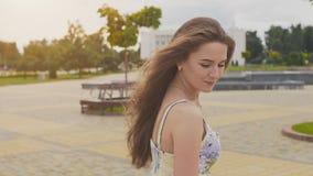 Powabna zmysłowa młoda dziewczyna w lato sukni chodzi wzdłuż parka w centrum miasto Jej długie włosy komarnicy zdjęcie wideo