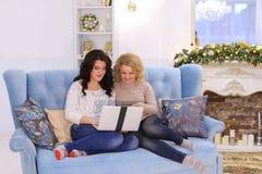 Powabne siostry decydowali troić filmu wieczór na laptopu sitti Obrazy Royalty Free