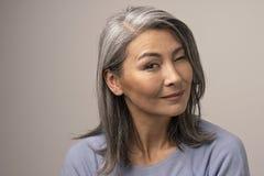 Powabnego azjaty dojrzała kobieta ono uśmiecha się przy kamerą obrazy royalty free