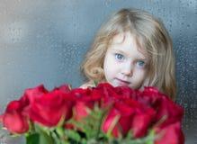 Powabnej blondynki Kaukaska dziewczyna patrzeje od behind czerwonych róż Naturalni raindrops na okno jako tło Zdjęcie Stock