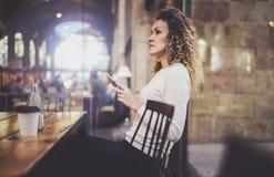Powabnej pięknej młodej kobiety czytelniczy e-mail na telefonie komórkowym podczas spoczynkowego czasu w sklep z kawą Bokeh i rac Fotografia Royalty Free
