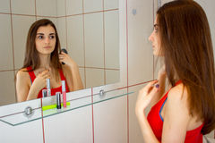 Powabni młoda dziewczyna stojaki przed lustrem i chwytami w jej ręce dla włosy grępla Zdjęcia Stock