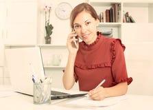 Powabny żeński pracownika odpowiadanie na telefonie i brać notatkach obrazy stock