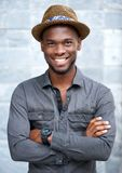 Powabny amerykanina afrykańskiego pochodzenia mężczyzna ono uśmiecha się z kapeluszem Zdjęcie Royalty Free
