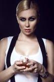 Powabny błękitnooki blondyn modeluje z ciągnącym z powrotem włosy trzyma szkło brandy Zdjęcia Royalty Free