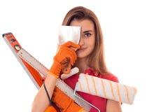 Powabny brunetki kobiety budowniczy w mundurze robi odświeżaniom przyglądający i ono uśmiecha się z narzędziami w jej rękach na k Fotografia Stock