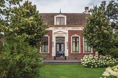 Powabny ceglany wieśniaka dom z kwitnącym zieleń gazonem w chmurnym dniu przy Drimmelen i ogródem zdjęcia stock