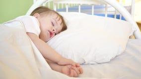 Powabny dziecko spada w domu uśpiony na białym łóżku w jego łóżku w pokoju pojęcie sypialny dziecko dziecko chce spać i zdjęcia royalty free
