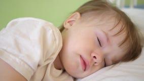 Powabny dziecko spada w domu uśpiony na białym łóżku w jego łóżku w pokoju pojęcie sypialny dziecko dziecko chce spać i zbiory